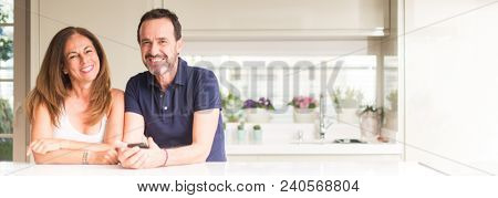 Middle age couple, woman and man using smartphone at kitchen. Ultra wide home shot.