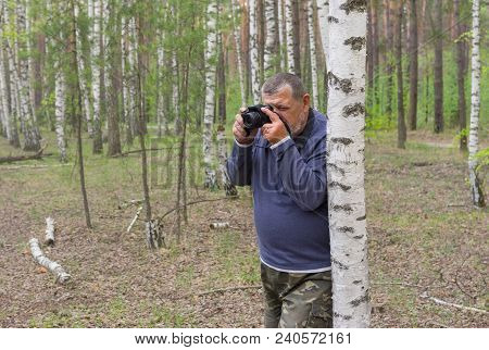 Elderly Man With Camera Standing Near Birch And Taking A Photo