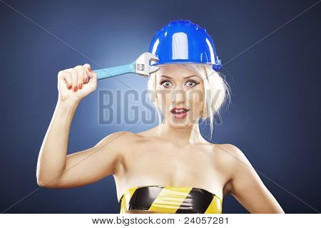 Beautiful Blonde With Construction Helmet And Adjustable Wrench.