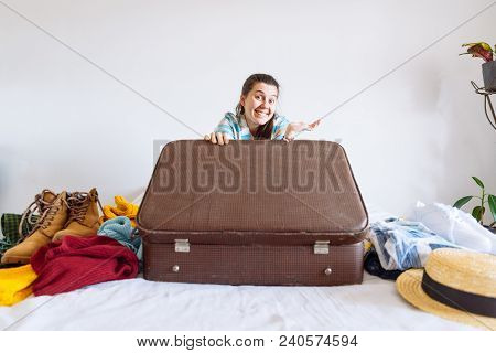 Woman Sit On Bed With Suitcase And Clothes Around. Travel Concept. Decide Warm Or Cold Country To Go