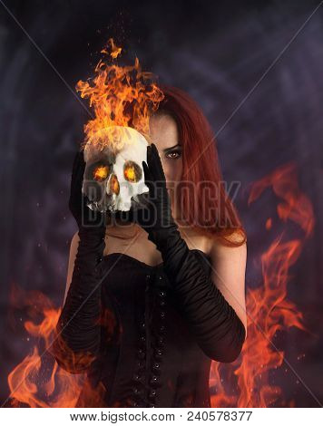 A Beautiful Redheaded Girl In Black Corset And Gloves Holding A Burning Human Skull.
