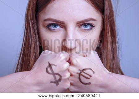 Fists Of A Young Beautiful Woman With A Dollar Euro Sign As A Symbol Of Confrontation Between Econom