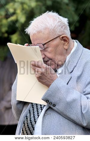 Kiev, Ukraine, 01.09.2012 A  Short-sighted Gray-haired Old Man In Glasses Reads Papers Keeping Them