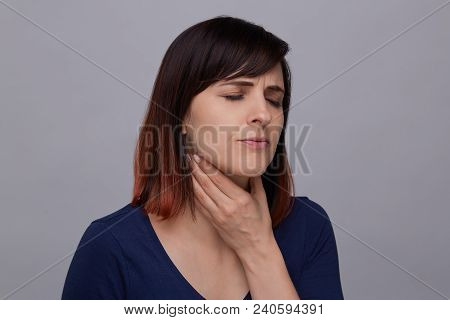 Young woman suffering from strong headache, holding fingers to her temples and closing eyes from pai