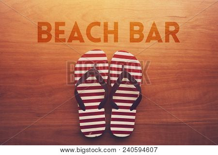 Beach Bar And Sandals Flip Flops On Wooden Background, Summer Holiday Vacation Concept