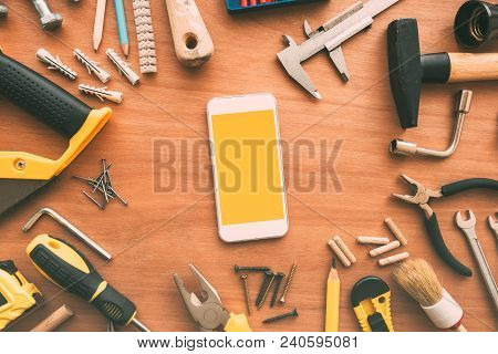 Smart Phone With Blank Screen On Repairman Workdesk. Copy Space For Text Or Handyman Maintenance Wor