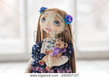 Close Up Portrait Of Textile Handmade Vintage Doll With Blue Eyes, Long Brown Hair In Old Blue Texti