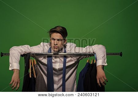 Man Put Hands On Rack With Clothes In Wardrobe. Businessman In White Shirt, Blue Tie On Green Backgr