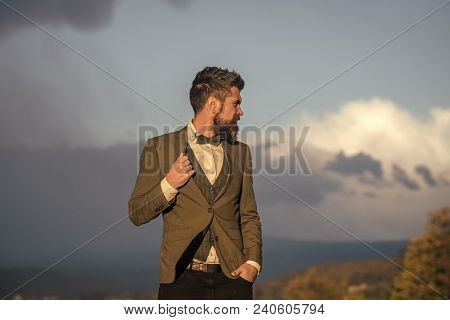 Hipster With Stylish Appearance In Front Of Dramatic Sky. Man With Beard And Mustache With Scenery O