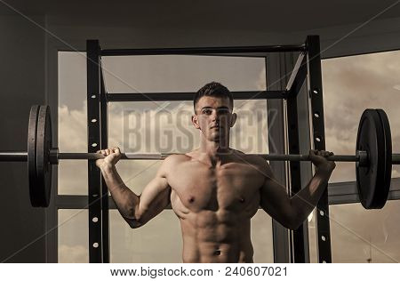 Sport And Gym Concept. Man With Torso, Muscular Macho Does Exercise With Barbell, Window On Backgrou