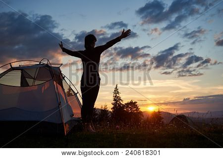 Rear View Silhouette Of Female Standing With Open Arms Near A Camping In The Mountains At Sunrise Un