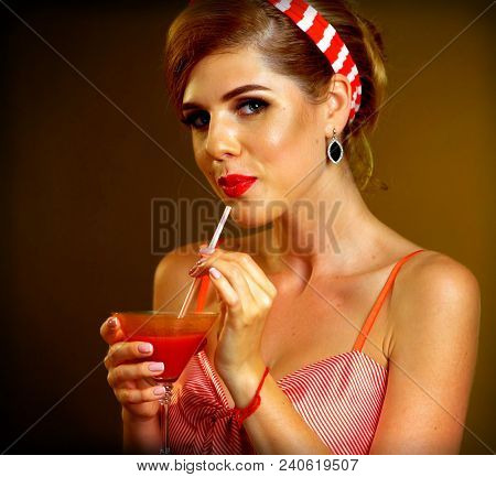 Retro woman with music vinyl record. Pin up girl drink martini cocktail. Girl pin-up retro style wearing red dress on dark background. Retro style looks very touching and beautiful.