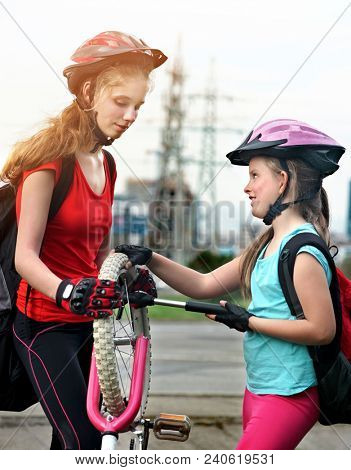 Bicycle tire pumping by child bicyclist. Girl wearing bicycle helmet with hand pump. Kids pump up tire. There are road and traffic sign at background. Children return home from school on bicycles. poster