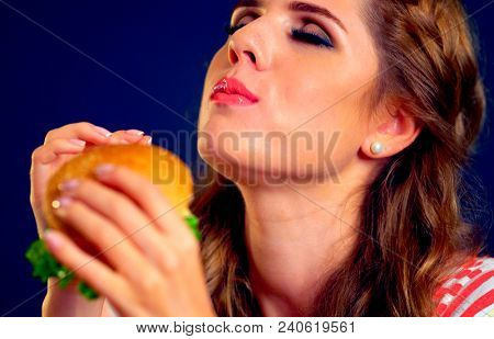 Woman eating burger and winks. Happy student going to seductively eat great sandwich for lunch. Joyful woman offers fast food on black background. Narcotic dependence on harmful products.