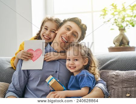 Happy father's day! Children daughters congratulating dad and giving him postcard and gift box. Daddy and girls smiling and hugging. Family holiday and togetherness.