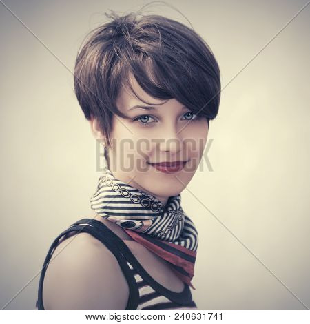 Happy young fashion woman with pixie hair walking in city street Stylish female model wearing tank top and silk scarf