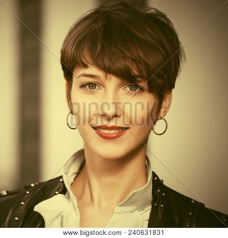 Happy young business woman walking in city street  Stylish fashion model wearing leather jacket with pixie hair