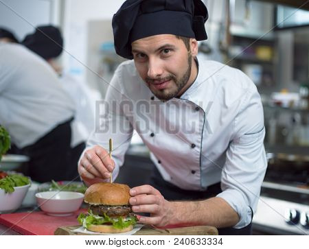 master chef putting toothpick on a burger in  restaurant kitchen