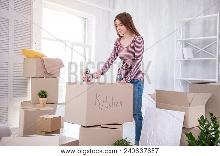 Ready To Move. Pretty Dark-haired Girl Taping The Box With Kitchen Cutlery While Packing Her Belongi