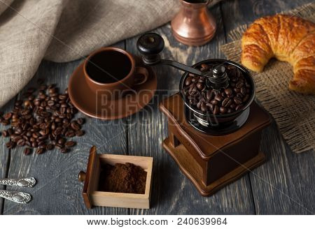 Manual Coffee Grinder, Ground Coffee In Box, Coffee Beans And Croissant On Dark Wooden Table