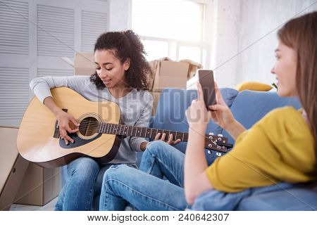 Song For You. Upbeat Curly-haired Girl Playing Guitar And Dedicating A Song To Her Roommate While Sh