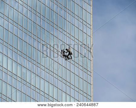 Window Cleaner On The Skyscraper Wall. Climber Wash Windows And Glass Facade Of The Skyscraper
