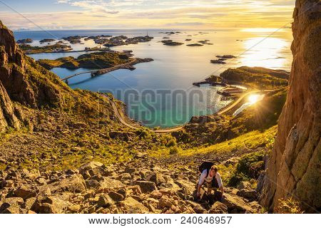 Young Hiker Going To The Top Of Mount Festvagtinden With Views Over The Village Of Henningsvaer On L