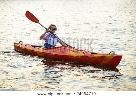 Young Woman Paddling Kayak on the Beautiful River or Lake at the Evening