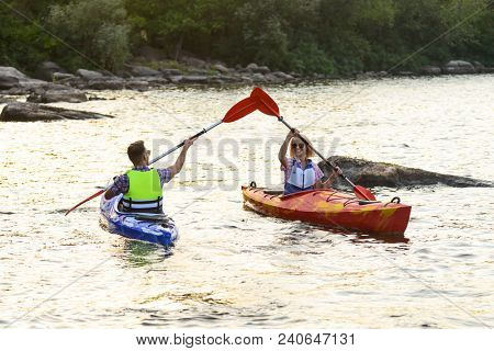 Young Happy Couple Paddling Kayak on the Beautiful River or Lake among Stones