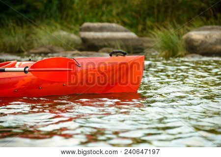 Close up Image of Red Kayak on the Beautiful River or Lake among Stones at the Evening