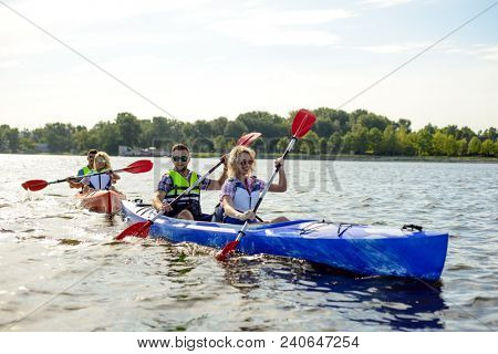 Friends Paddling Kayaks on the Beautiful River or Lake