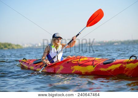 Young Professional Woman Kayaker Paddling Kayak on the River under Bright Morning Sun. Sport and Active Lifestyle Concept