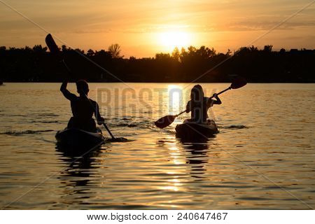 Young Couple Paddling Kayaks on the Beautiful River or Lake under the Dramatic Evening Sky at Sunset