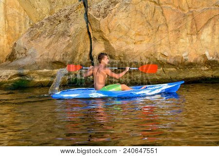 Young Man Paddling Blue Kayak on the Beautiful River or Lake under High Rock in the Evening