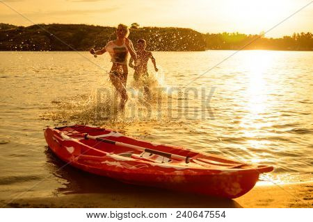 Young Couple Playing and Having Fun in the Water on the Beach near Kayak under the Dramatic Evening Sky at Sunset