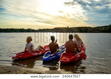 Friends Resting and Talking while Sitting in Kayaks on the Beautiful River or Lake Beach under the Dramatic Evening Sky at Sunset