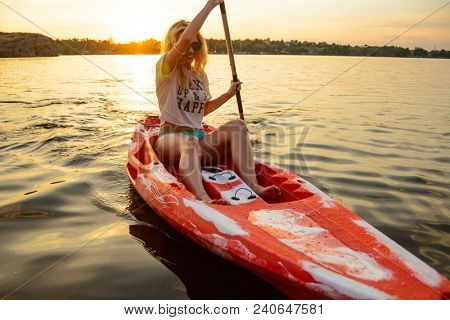Young Happy Woman Paddling Kayak on the Beautiful River or Lake at Sunset