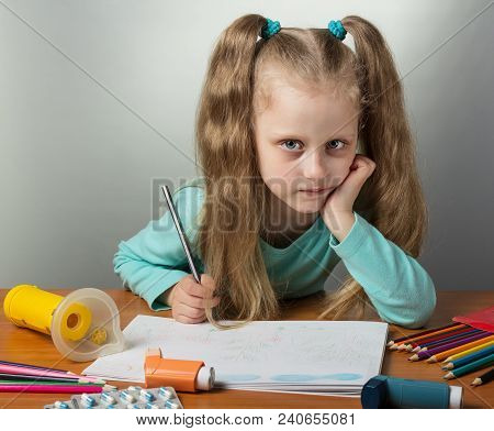 Little Sick Girl Draws Sitting At Table, Next To An Inhaler With Dispenser And Mask