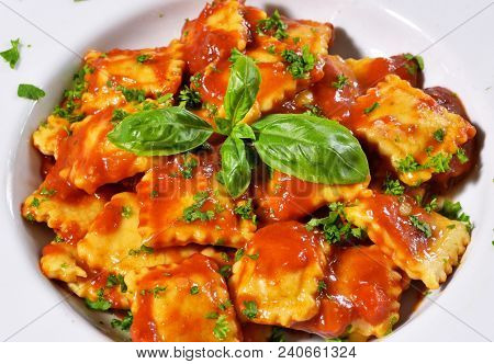 Fresh Ravioli Pasta With Parsley And Basil Leaf, Italian Cuisine. White Plate And Wooden Table, Past