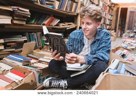Positive Student Sitting On The Floor In An Old Public Library And Reading Books. A Young Man Enjoys
