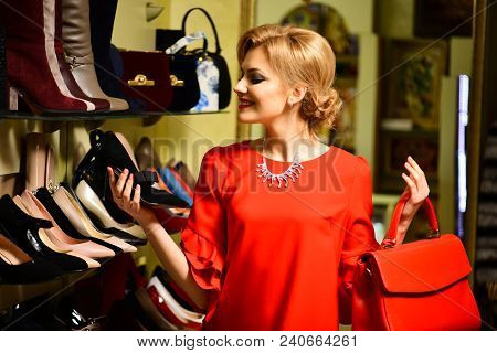 Woman In Red With Smiling Face With Shopping Mall On Background. Girl With Makeup Looks At High Heel