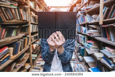 A Young Man Stands In A Cozy, Old, Public Bulletin And Holds A Book In Front Of His Face. The Studen