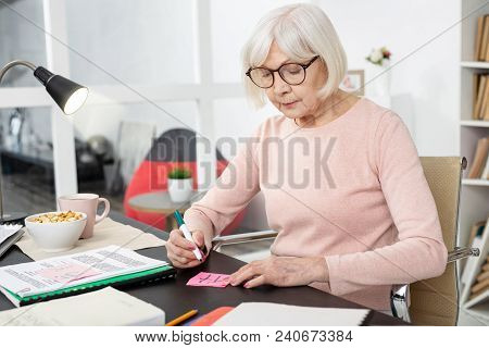 Remember Hieroglyph. Attractive Mature Woman Writing Hieroglyph Assorted On Sticker And Looking Down