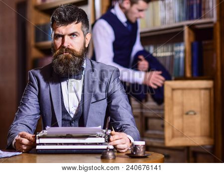 Writers Routine Concept. Writer Working On New Book With Bookshelves On Background. Man With Beard A