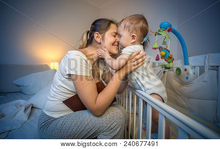 Happy Smiling Woman Hugging Her Baby Son Standing In Cot At Night
