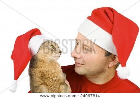 Young Man And Cat In Santa's Hat Looking At Each Other, Isolated