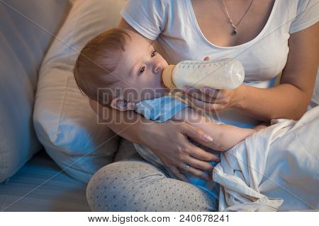 Portrait Of 9 Months Old Baby Boy Eating Milk From Bottle At Night