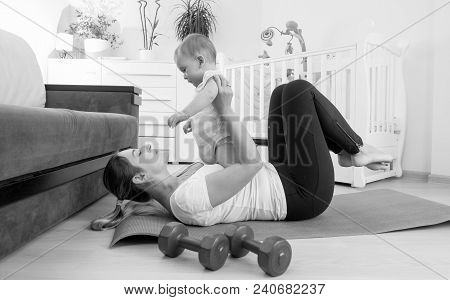 Black And White Photo Of Young Woman Exercising With Her 9 Months Old Baby Son At Home