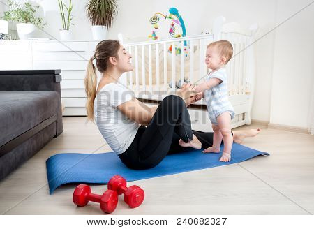 9 Months Old Baby Boy Exercising With Young Mother On Fitness Mat At Home