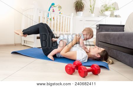 Baby Boy Sitting On Young Mother Exercising On Fitness Mat At Home
